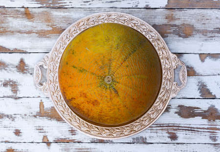 goldish: ripe melon on a golden platter on an old white wooden table, top view close-up Stock Photo