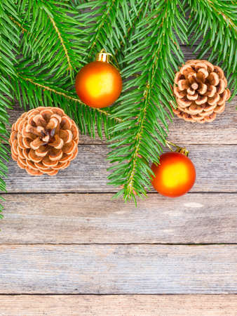 goldish: New Year or Christmas background: fir branches, goldish glass balls cones over old wooden backdrop, top view, copy space Stock Photo