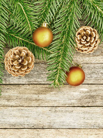 goldish: New Year or Christmas background: fir branches, goldish glass balls cones over old wooden backdrop, top view, copy space, tinted photo