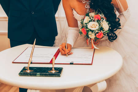 Wedding. Registration Of Marriage, The Bride With A Bouquet Of Flowers Signed A Marriage Contract A Golden Pen, Selective Focus. Tinted Image 写真素材