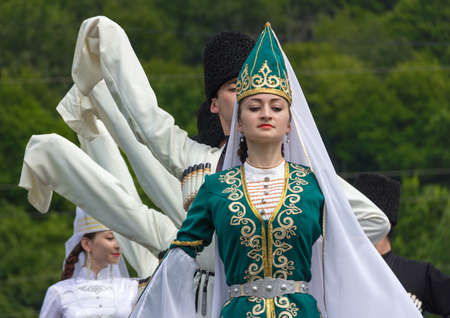 ADYGEA, RUSSIA - JULY 25 2015: Adyghe boys and girls in national costumes dance on the Circassian ethnic festival in the mountains of Adygea