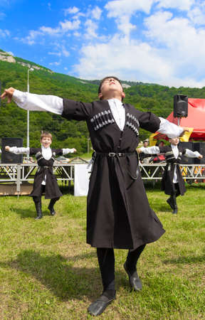 ADYGEA, RUSSIA - JULY 25 2015: Adyghe boy in Circassian national costumes dance to the ethnic festival in the mountains of Adygea