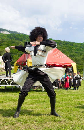 ethnic festival: ADYGEA, RUSSIA - JULY 25 2015: Adyghe guy in Circassian national costumes dancing on ethnic festival in the mountains of Adygea