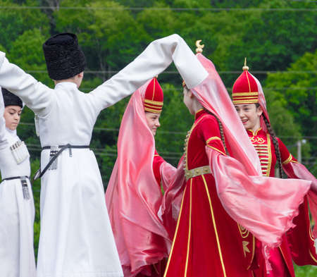 ethnic festival: ADYGEA, RUSSIA - JULY 25 2015: Adyghe girls and boys in national costumes dance to the Circassian ethnic festival in Adygeya Editorial