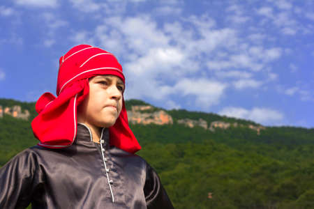 ADYGEA, RUSSIA - JULY 25 2015: Portrait adyghe boy in Circassian national dress on a background of mountains and blue sky on ethnic festival in Adygeya Editorial