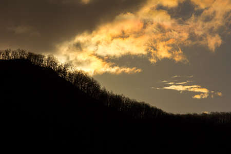 setting  sun: silhouette of mountains with trees against cloudy sky with the last rays of the setting sun