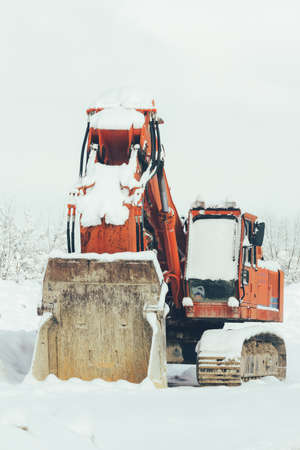 joblessness: excavator standing in the snow winter outdoors, close-up. The concept of unemployment, the failure of