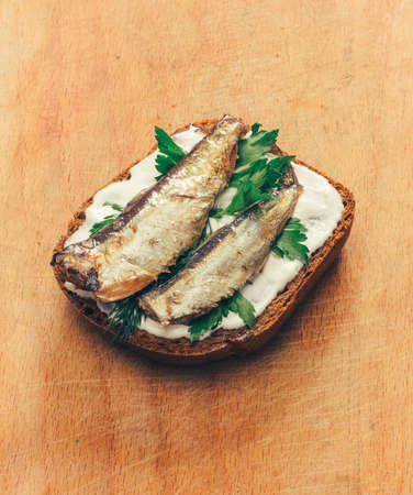 tinned goods: sandwich of canned sprats on rye bread with mayonnaise and parsley, and dill on a wooden cutting board close up