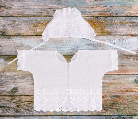 coif: cap and shirt for a newborn on the old rustic wooden table close-up, top view Stock Photo