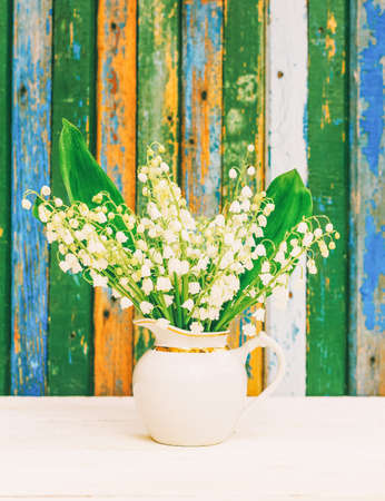 A bouquet of white fragrant forest flowers of lilies of the valley in a white jug on a table on the background of a wall of granary boards