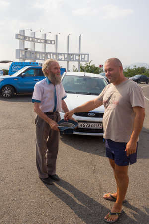 Novorossiysk, Russia - July 27, 2016 - Tourist gives alms to a bearded man the beg with the hat in the Parking lot at the entrance to the city Editorial