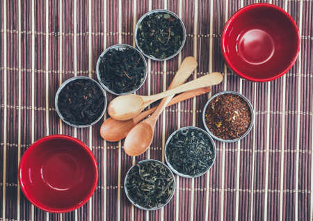 a selection of teas, red cups and wooden spoons on bamboo Mat, top view