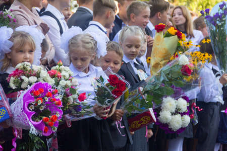 Adygea, Russia - September 1, 2017: children with bouquets of flowers enrolled in the first grade with high school students at school the solemn ruler in day of knowledge