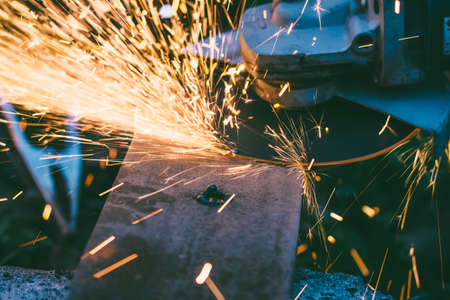 power: sparks flying from under the rotating disc grinder when cleaning steel parts after welding