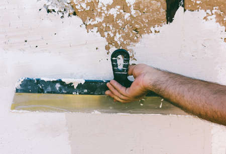 surface: hairy hand guest worker with a steel spatula plastering the wall