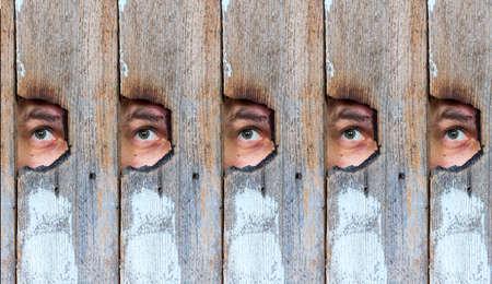 人間の目は、古い木の塀の穴からスパイ盗撮の抽象的なコラージュ
