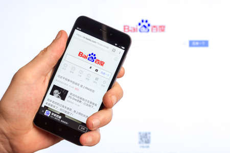 Adygea, Russia - January 4, 2018: home page of the popular website Chinese search engine company Baidu on the screen of the Chinese smartphone Xiaomi in the male hand 報道画像