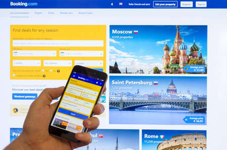 Adygea, Russia - January 16, 2018: The home page of the Internet booking of hotels booking.com on the screen the Chinese Xiaomi smartphone in male hand on a computer monitor 報道画像
