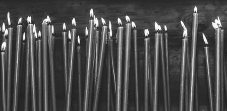 many burning wax candles in the temple, black and white photo Stock Photo