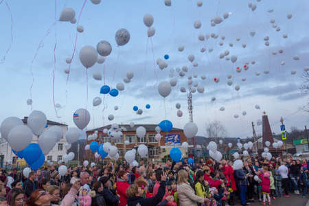 Adygea, Russia - March 28, 2018: people are launching into the sky white balloons on the day of mourning for those killed in a fire in the city of Kemerovo