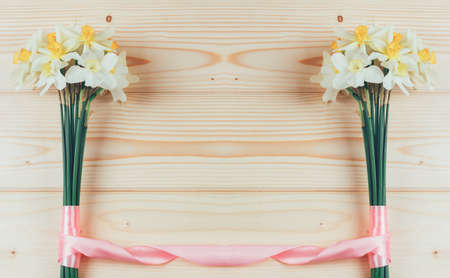 frame of bouquets of daffodils flowers tied with pink ribbon on a natural wooden background with copy space for text