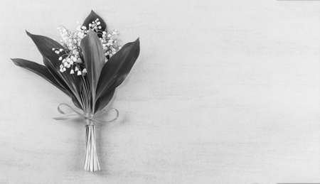 bouquet of Lily of the valley flowers tied with ribbon on gray background with copy space, black and white photo