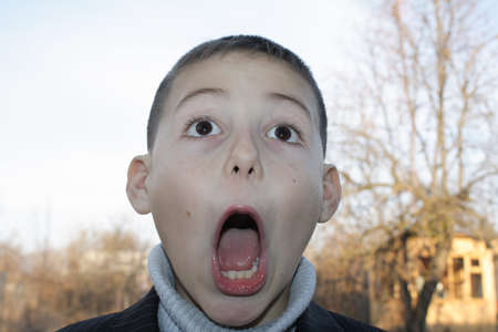 8 year old boy with black eyes depicting strong amazement wide open mouth