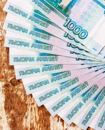 Russian banknotes in denominations of 1000 rubles are spread out on a fan on a wooden grunge background