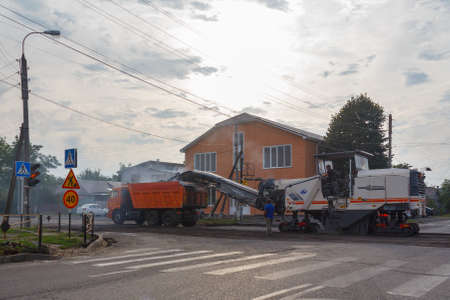 Maikop, Russia - October 2, 2015: workers and special equipment perform road repair work, remove the old asphalt