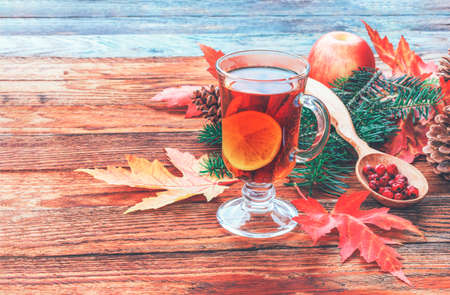 still life with tea cinnamon and lemon, ripe apples, red autumn maple leaves, fir branch and pine cones and hawthorn berries in a wooden spoon on table closeup Stock fotó
