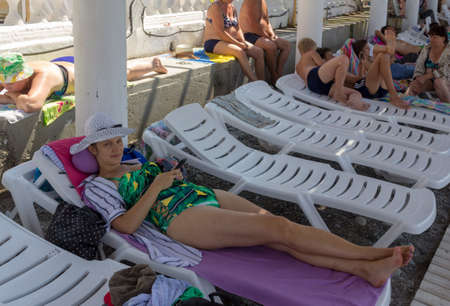 Sochi, Russia - August 21, 2018: young attractive girl in a hat with a mobile phone in her hands lying on a chaise longue Editorial
