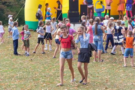 Kamennomostsky, Russia - September 1, 2018: Animators on stage entertain children at the festival day of the village of Kamennomostsky in the autumn park Editorial