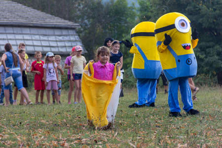 Kamennomostsky, Russia - September 1, 2018: Animator in the costume of a minion playing with the children on the feast day of the village of Kamennomostskiy in the autumn Park