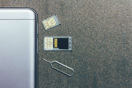 mobile phone and open slots for nano SIM cards, micro SD drive and metal key on grey background with copy space