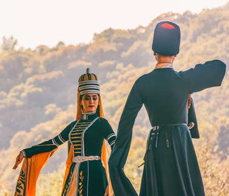 Dakhovskaya, Russia - September 22,  2018: a guy with a girl in traditional Circassian clothes dancing at the festival of Adyghe cheese in the foothills of the Caucasus