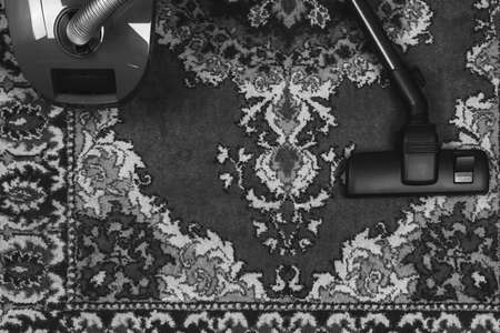 electric vacuum cleaner on the background of an old carpet, top view of flat lay, black and white photo