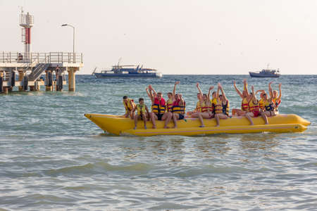 Sochi, Russia - August 21, 2018: a group of tourists at the sea sitting on an inflatable banana and waving their hands Editorial