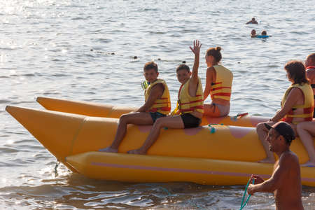 Sochi, Russia - August 21, 2018: teenage boys, girl and man with a woman sitting on an inflatable banana in the sea 報道画像