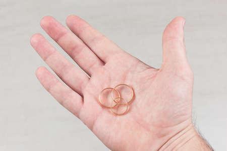 three gold wedding rings on the male palm Standard-Bild