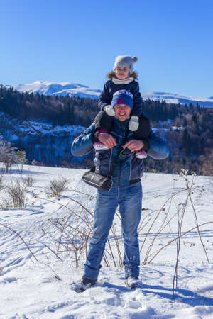 Adygea, Russia - January 23,  2017: little daughter sits on her father's shoulders on a winter day at a ski resort Stock Photo - 114570179