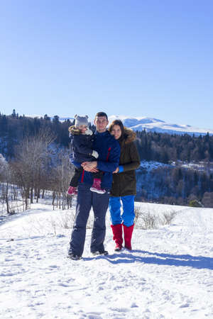 Adygea, Russia - January 23,  2017: a young family with a daughter on a winter day at a ski resort