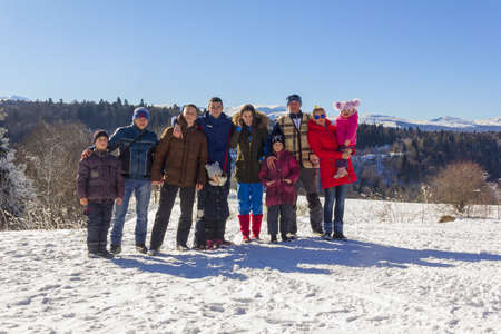 Adygea, Russia - January 23,  2017: a group of happy tourists with children on a background of snowy mountains on a Sunny winter day Editorial