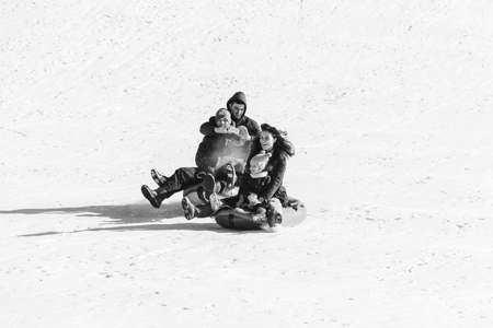 Adygea, Russia - January 23,  2017: Young happy couple with children riding on inflatable sledding tubing on a snowy slope, a man shoots a video on a smartphone, black and white photo Editorial