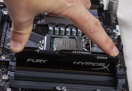 Maykop, Russia - November 9, 2018: man installs an DDR 4 DIMM 16 Gb Kingston HyperX Fury Memory RAM Module in the slot on the motherboard closeup Stock Photo - 114570194
