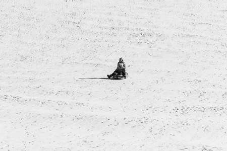 Adygea, Russia - January 23,  2017: A young mother with a little daughter rides on an inflatable sledding tubing on a snow slope, black and white photo Stock Photo - 114570213
