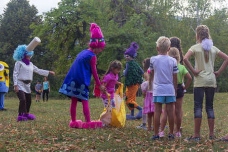 Kamennomostsky, Russia - September 1, 2018: Holiday day of the village with animators and childrens playgrounds and competitions in the park in the fall