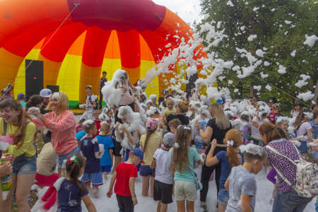 Kamennomostsky, Russia - September 1, 2018: Happy children having fun at a foam party at a holiday town day in an autumn park