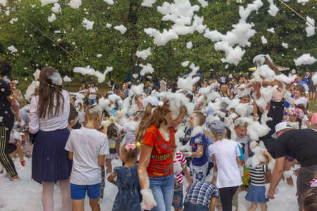Kamennomostsky, Russia - September 1, 2018: Happy children having fun at a foam party at a holiday town day in an autumn park Stock Photo - 114570340