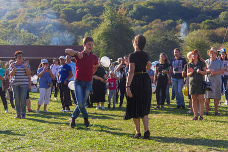 Dakhovskaya, Russia - September 22,  2018: young guy and girl dancing in the meadow at the Adygei cheese festival in the foothills of the Caucasus Stock Photo - 114570363
