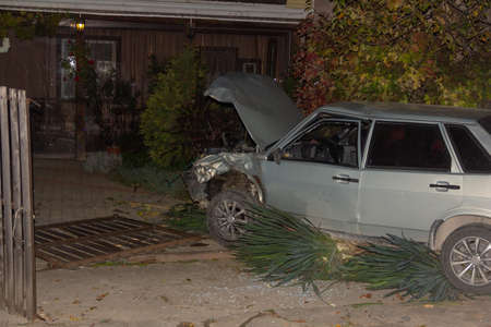 broken car in the flower bed and a damaged fence in a private home after a night in a car accident Stock Photo - 114612501